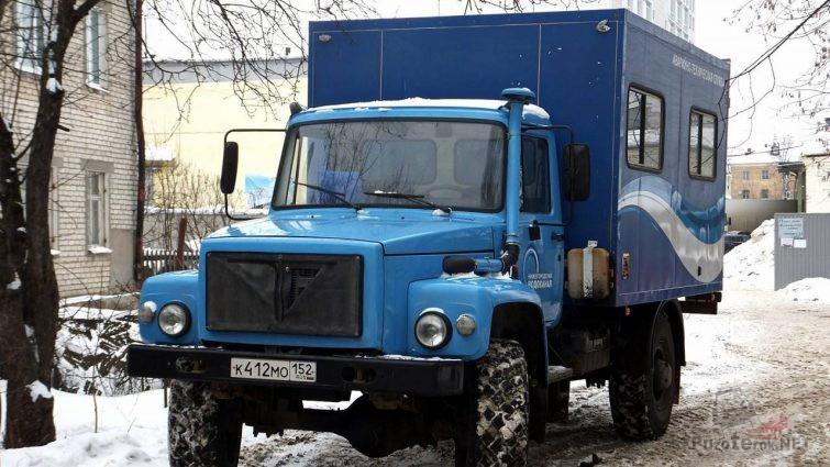Синий грузовик компании Водоканал с кунгом на зимней улице