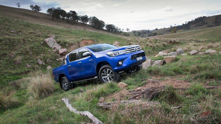 Синий пикап поднимается по склону на природе