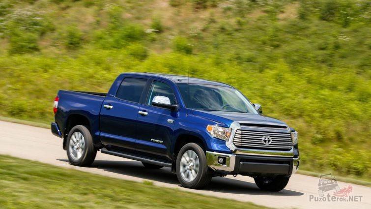 Синяя Тойота едет по дороге за городом