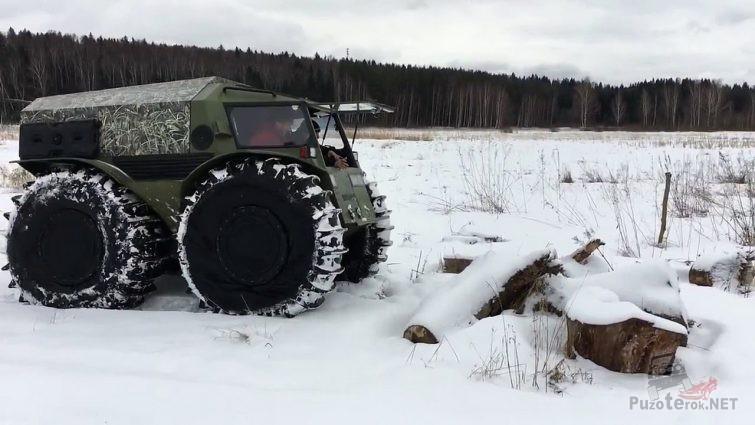 Снегоболотоход Шерп перед брёвнами в зимнем поле