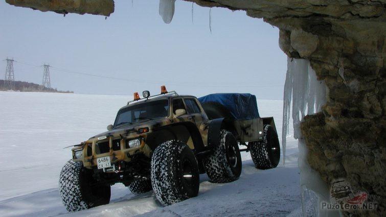 Снегоболотоход с мигалками и прицепом возле пещеры
