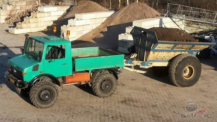 Старенький грузовик с полным прицепом земли