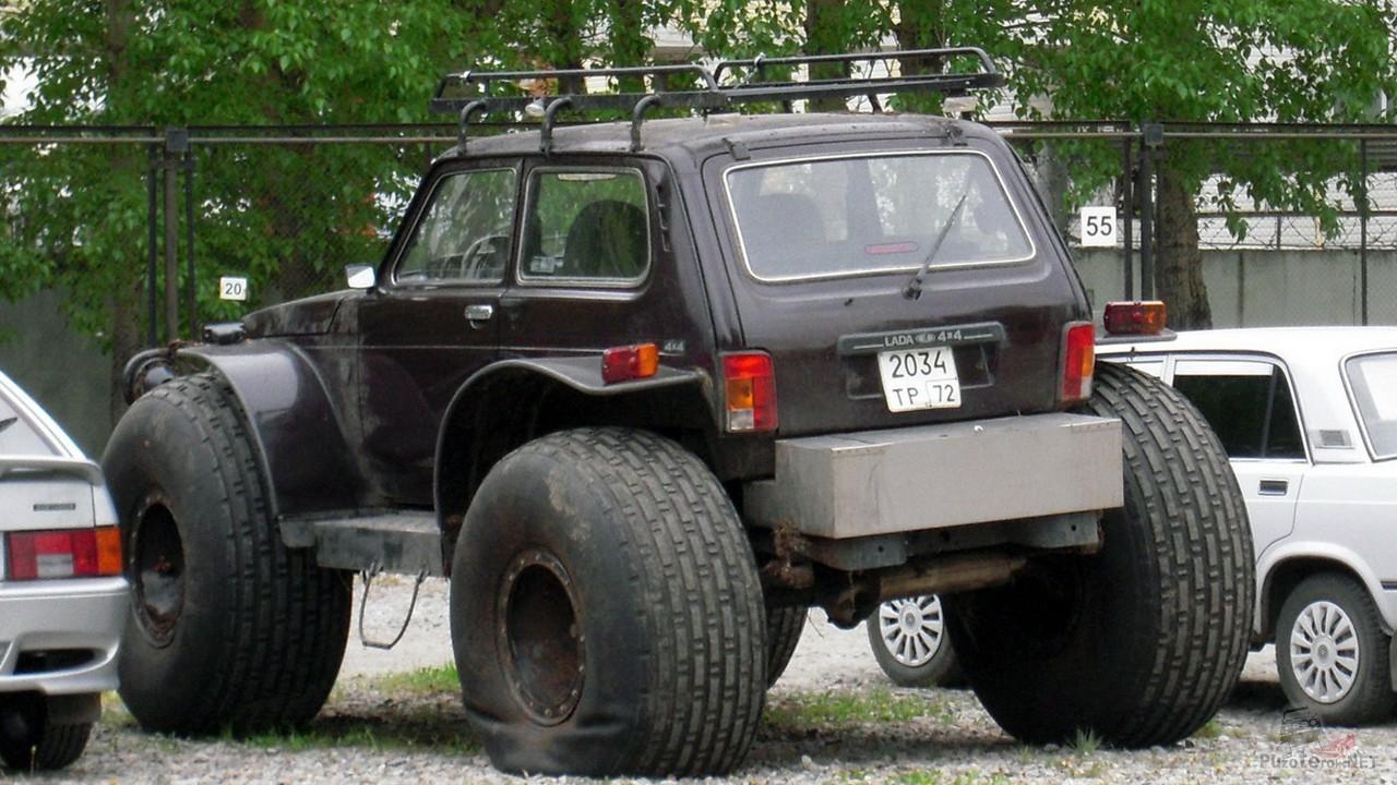 Тёмная Лада с большими колёсами на стоянке