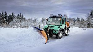 Унимог со снежным отвалом чистит трассу