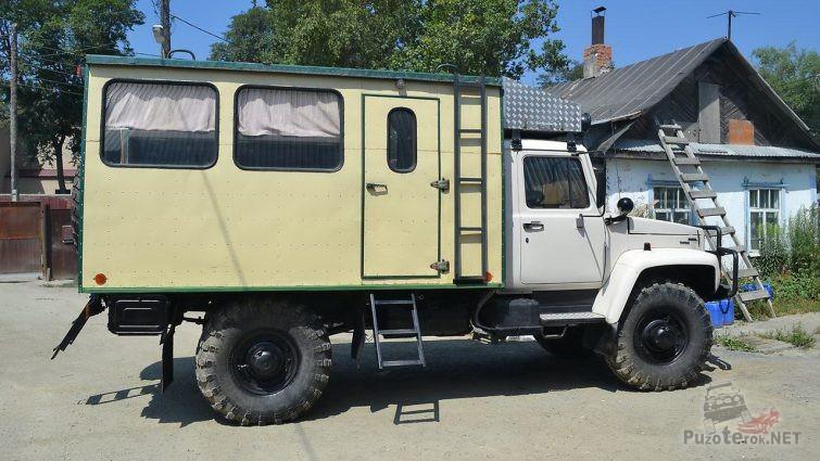 Вид сбоку грузовика с жёлтым кунгом в частном секторе
