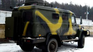 Вид сзади грузовика Вепрь жёлто-болотного цвета на снегу