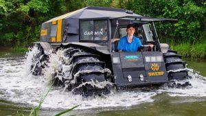 Водитель управляет вездеходом в реке
