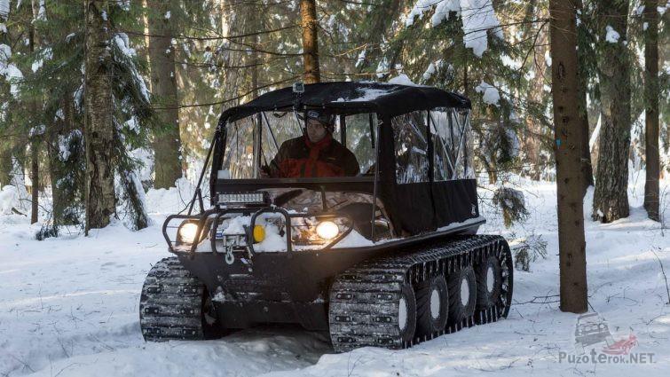 Водитель вездехода с кабиной в зимнем лесу