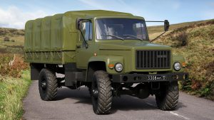 Военный грузовик Садко бортового типа на дороге за городом