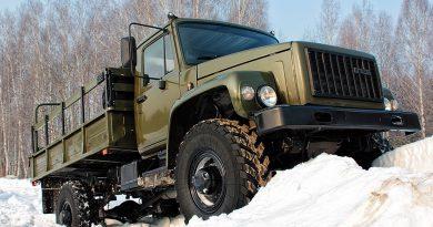 Военный грузовик взбирается по снегу на горку