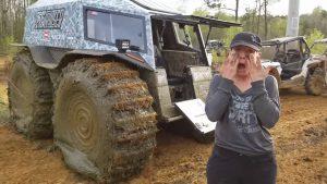 Женщина вытирает лицо от грязи возле грязного вездехода