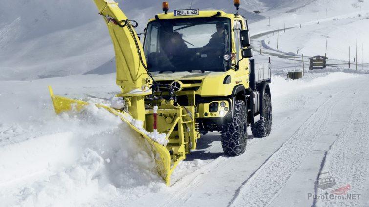 Жёлтая спецтехника убирает снег на дороге