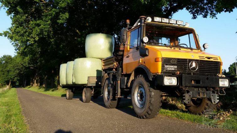 Жёлтый грузовик с грузом в прицепе на обочине дороги