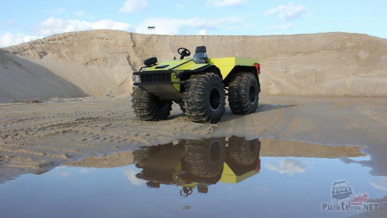 Жёлтый вездеход в песчаном карьере возле лужи