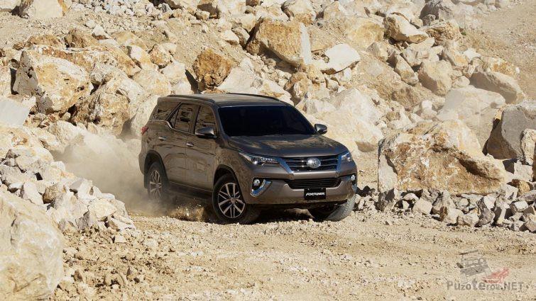 Автомобиль Тойота едет по каменистой дороге