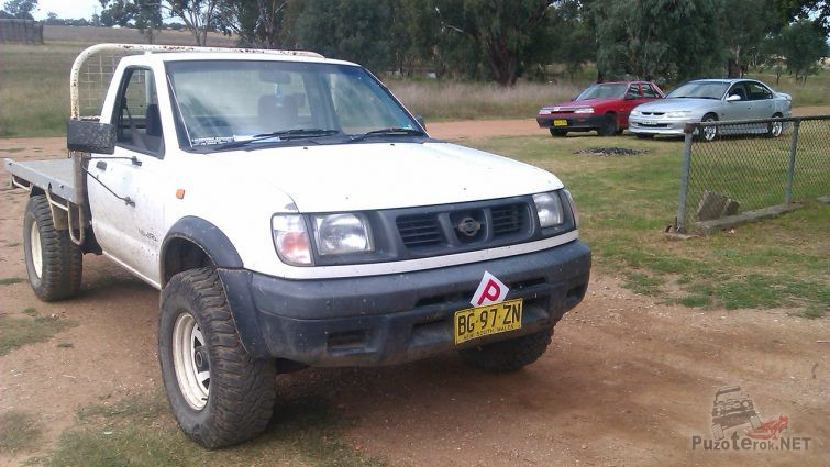 Белый Nissan Navara второго поколения с площадкой