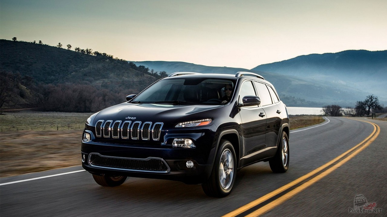 Чёрный Jeep Cherokee едет по шоссе