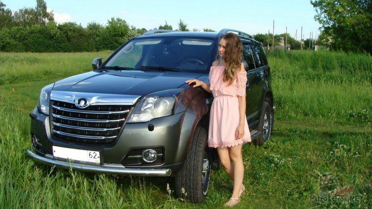 Девушка возле автомобиля на траве