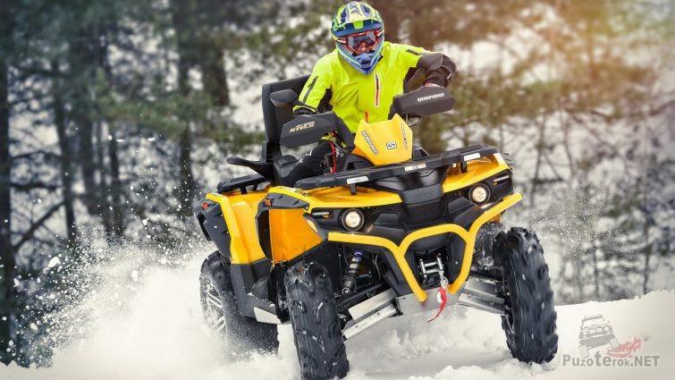 Мужчина в каске едет по снегу на квадроцикле