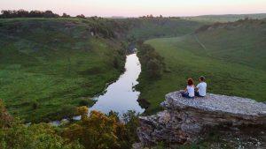 Парень с девушкой медитируют на Воргольской скале у обрыва