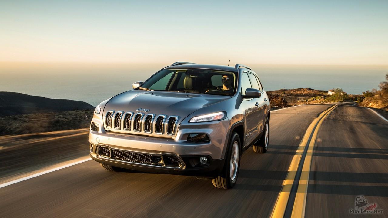 Серый Jeep Cherokee едет по шоссе за городом