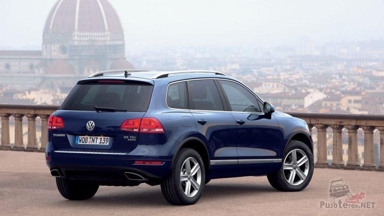 Синий Volkswagen Touareg над городом
