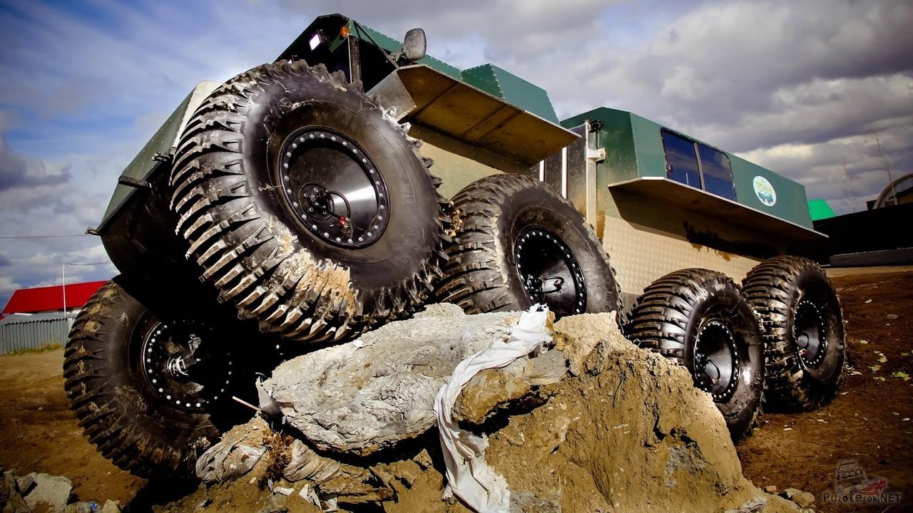 Снегоболотоход забрался передними колёсами на камень