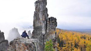 Турист сидит на высокой скале