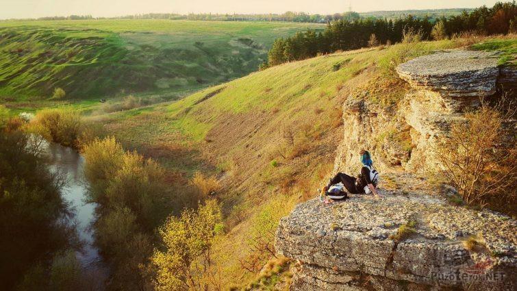 Туристка сидит на Воргольской скале