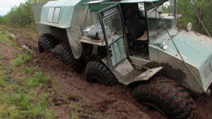 Тёмно-зелёный болотоход погряз в торфяной дороге