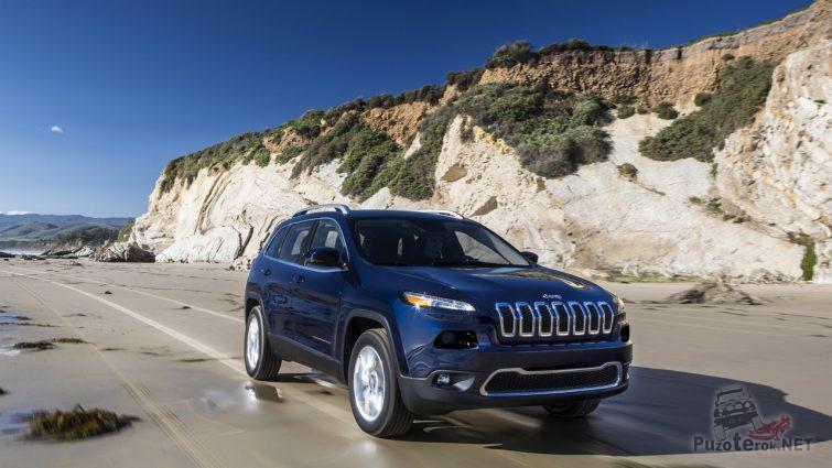 Тёмный Jeep Cherokee едет вдоль скалы