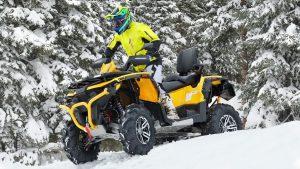 Водитель квадроцикла на фоне снежных елей