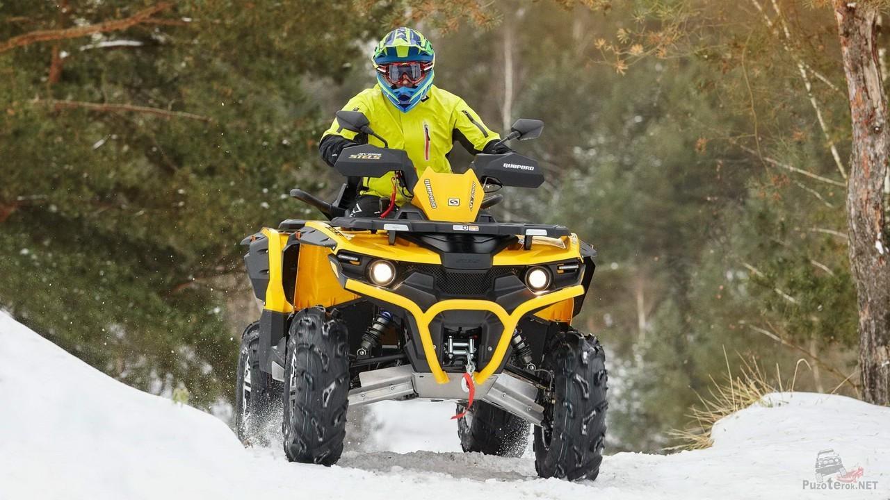 Водитель квадроцикла на зимней дороге