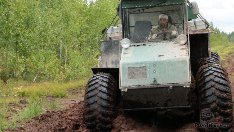 Водитель за рулём болотохода на торфянике