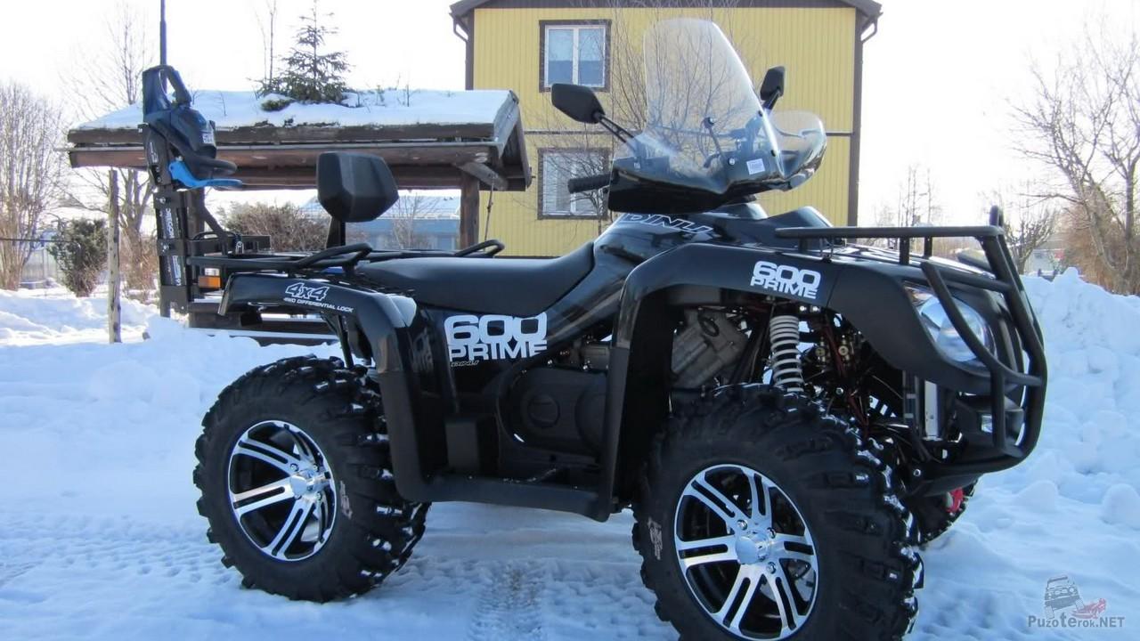Чёрный квадроцикл на снегу у дома