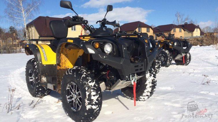 Квадроциклы на снегу на фоне домиков