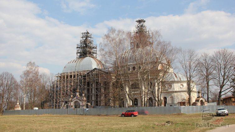 Автомобили туристов у реставрируемого здания церкви