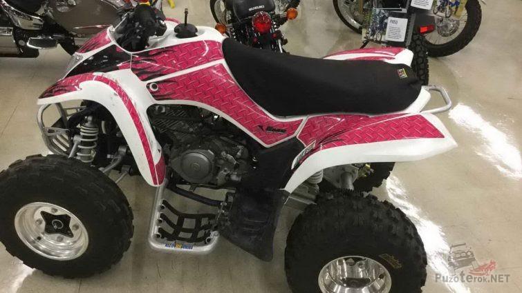 Бело-розовый квадроцикл возле другой техники