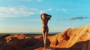 Блондинка в бикини на вершине скалы