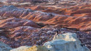 Девушка на вершине скалы над пёстроцветными сопками