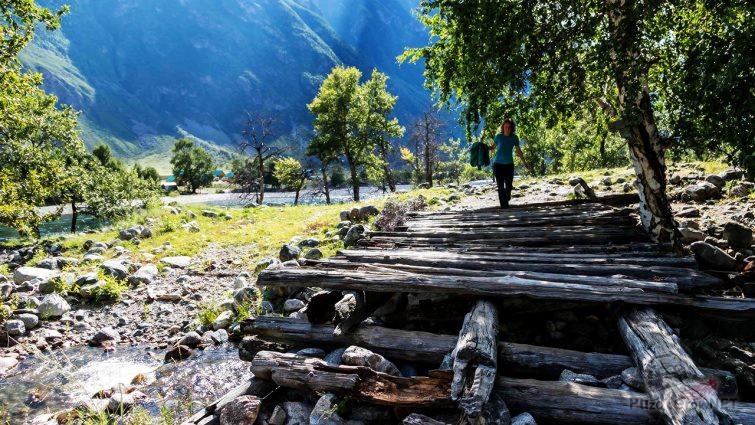 Девушка переходит по мосткам через речку в долине Чулышмана