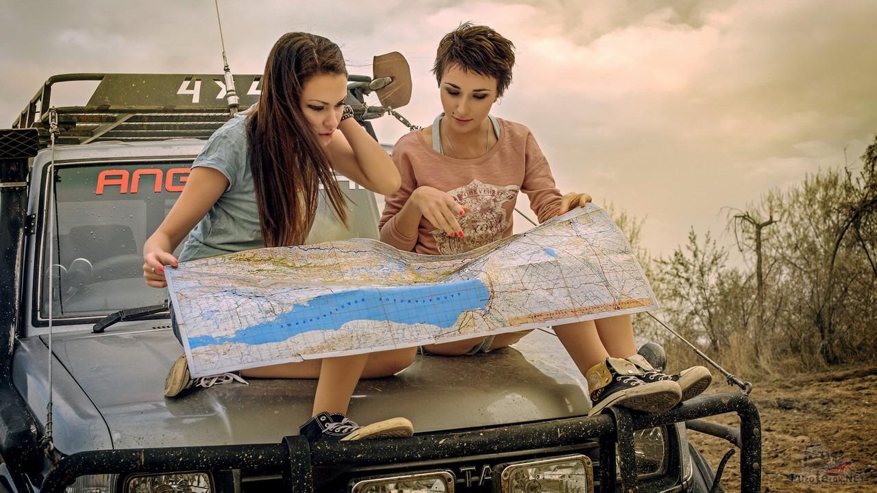 Девушки рассматривают карту на капоте внедорожника