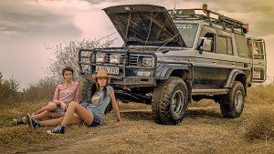 Девушки сидят перед подготовленным внедорожником