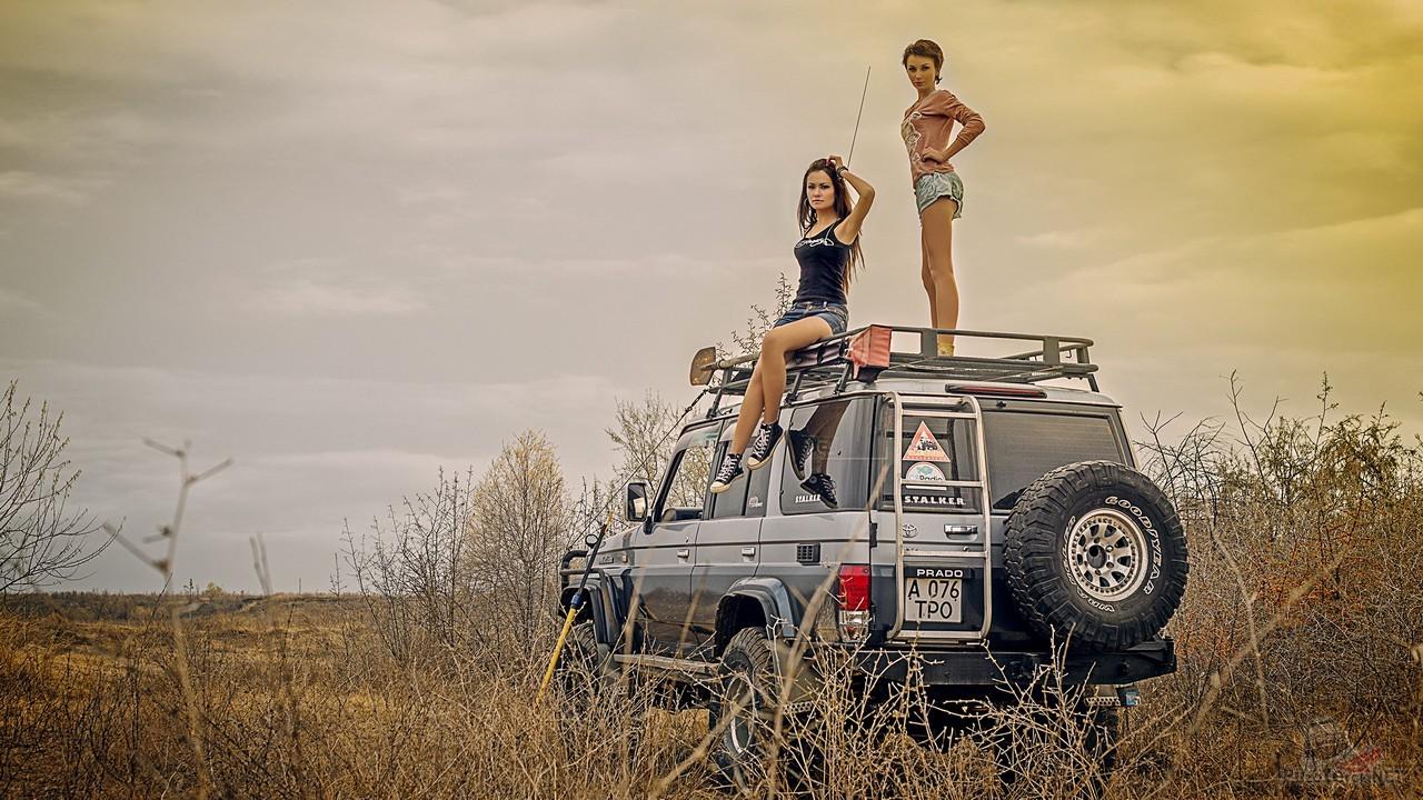 Две девушки на багажнике внедорожника
