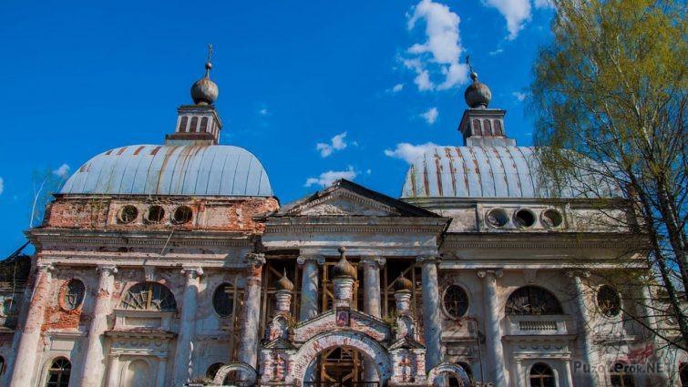 Фронтон и купола заброшенной церкви на фоне ясного неба