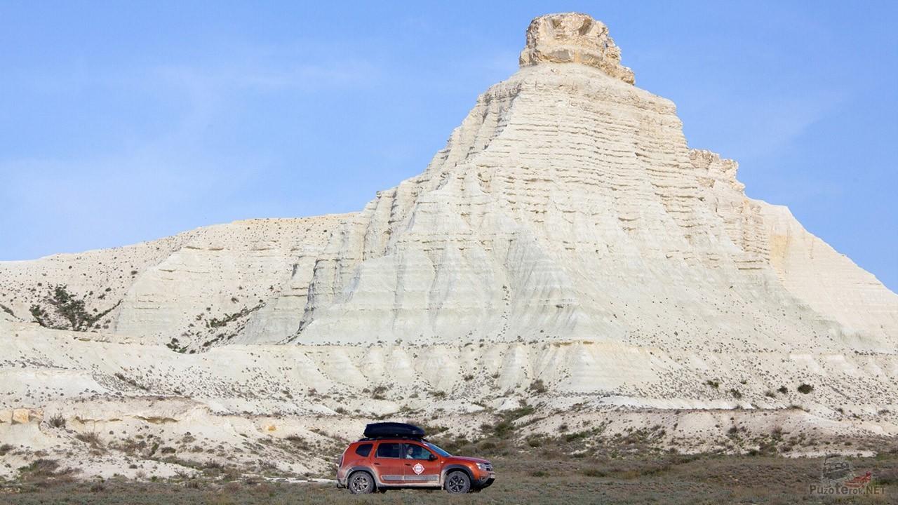 Красный внедорожник у белой скалы