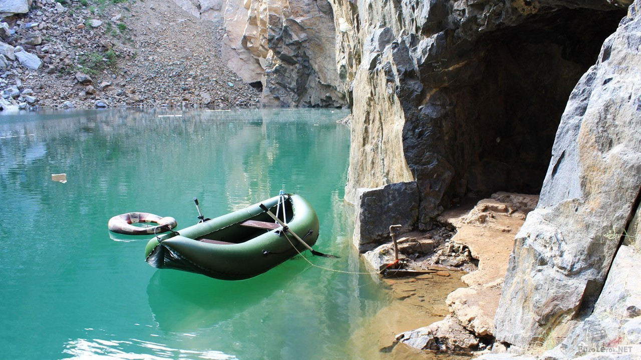 Лодка экстремальных туристов у подножья скалы