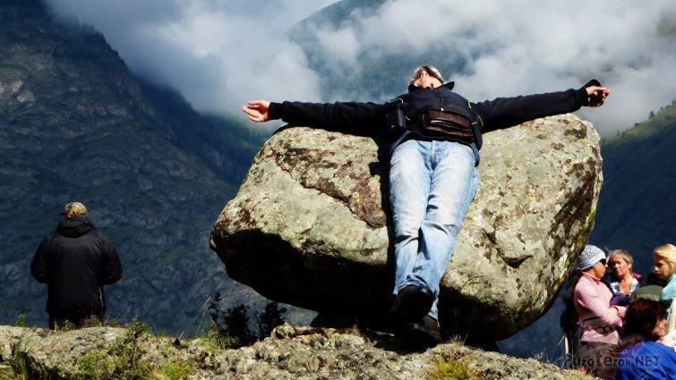 Турист лежит, раскинув руки на валуне - шляпке гриба