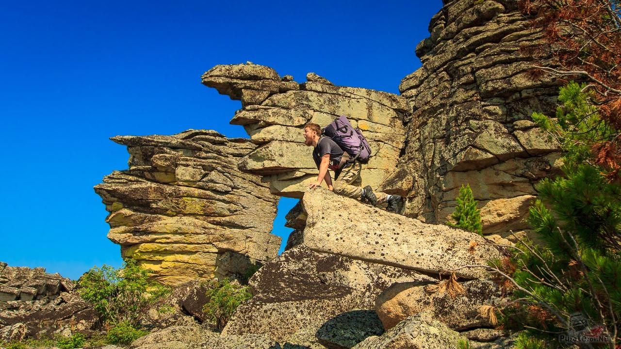 Турист на скале изображает льва