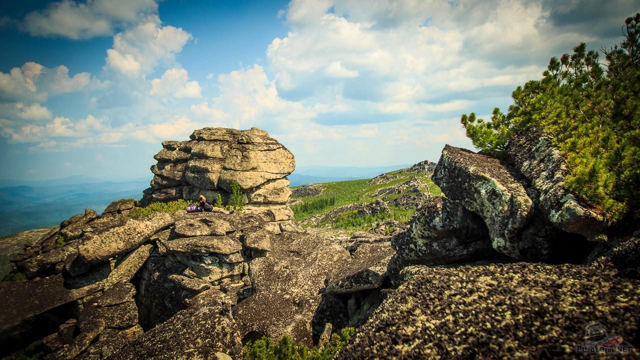 Турист отдыхает на вершине скалы